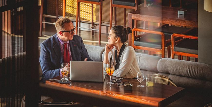 Young business woman and man having a business conversation at a restaurant. They both are well dressed and in a good mood. There is an open laptop on the table before them. Selective focus, waist up, copy space has been left.